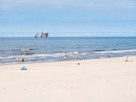 People on beach and North Sea with offshore drilling platform, West Frisian island Ameland, Friesland, Netherlands Stock Photo - 119031255
