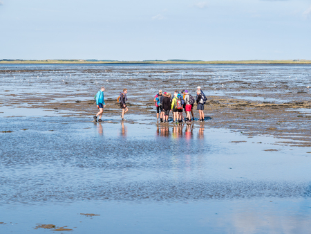 Group of people mud flat hiking on Wadden Sea at low tide from Friesland to West Frisian island Ameland, Netherlands Stock Photo - 119031256