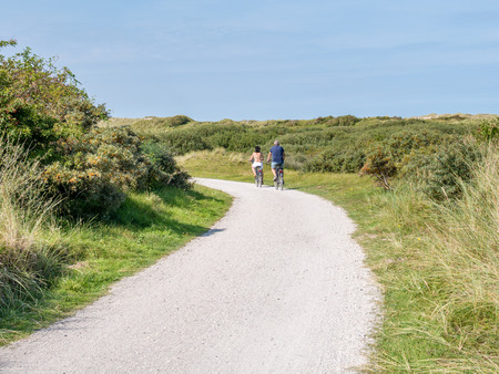 Rear view of people riding bicycles on bicycle path in dunes of nature reserve Het Oerd on West Frisian island Ameland, Friesland, Netherlands Stock Photo - 119031261
