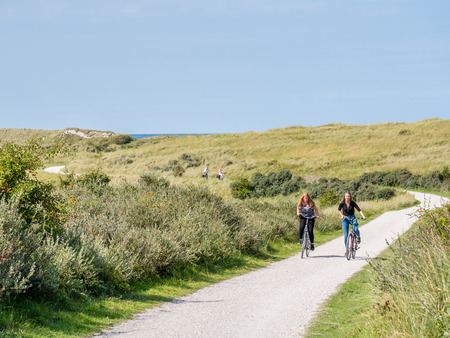 People riding bicycles on bicycle path in dunes of nature reserve Het Oerd on West Frisian island Ameland, Friesland, Netherlands Redactioneel