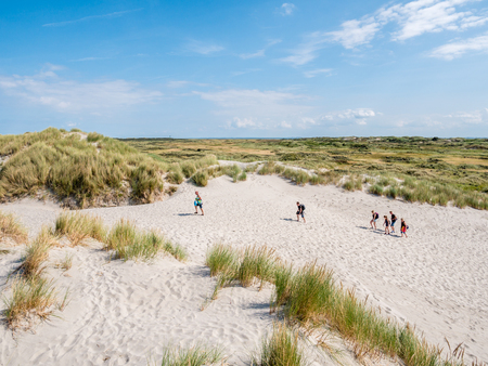 Panorama of dune landscape with people walking in nature reserve Het Oerd on West Frisian island Ameland, Friesland, Netherlands
