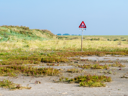 Warning sign for dangerous quicksand in salt marshes of coast of West Frisian island Schiermonnikoog at low tide of Wadden Sea, Netherlands