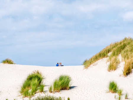 Rear view of two people sitting together relaxing on sand dune in nature reserve Het Oerd on West Frisian island Ameland, Friesland, Netherlands Stock Photo