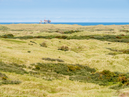 Panorama of dunes of nature reserve Het Oerd and offshore platform in North Sea off coast of West Frisian island Ameland, Friesland, Netherlands