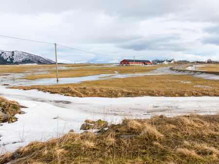 Power lines, farmhouse and road of Bitterstad at countryside of Langoya, Vesteralen, Nordland, Norway