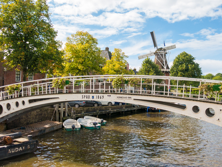 DOKKUM, NETHERLANDS - SEP 9, 2017: Windmill Zeldenrust and bridge over Kleindiep canal in historic old town of Dokkum, Friesland, Netherlands