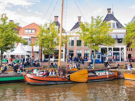 DOKKUM, NETHERLANDS - SEP 9, 2017: Quayside with people and historic ships in old harbour during event Admiralty Days, Dokkum, Friesland, Netherlands