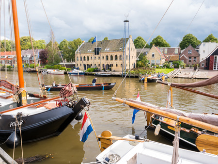 DOKKUM, NETHERLANDS - SEP 7, 2017: Historic harbour with boats and old slipway during event Admiralty Days, Dokkum, Friesland, Netherlands