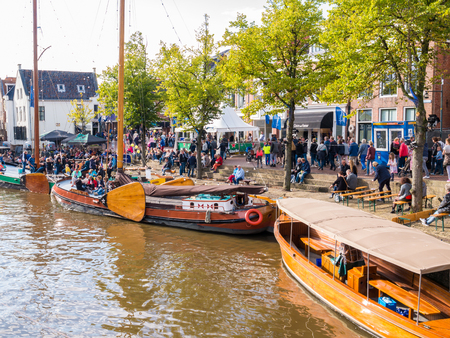 DOKKUM, NETHERLANDS - SEP 9, 2017: People and historic ships in old harbour during event Admiralty Days, Dokkum, Friesland, Netherlands