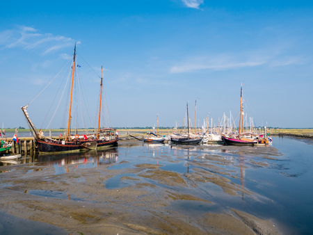 SCHIERMONNIKOOG, NETHERLANDS - AUG 29, 2017: Sailing boats in marina at low tide, West Frisian island Schiermonnikoog, Netherlands