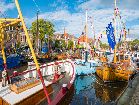 DOKKUM, NETHERLANDS - SEP 9, 2017: Historic harbour with decorated boats during event Admiralty Days in old town of Dokkum, Friesland, Netherlands
