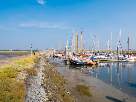 SCHIERMONNIKOOG, NETHERLANDS - AUG 29, 2017: People, motorboats and sailboats in marina of West Frisian island Schiermonnikoog, Friesland, Netherlands