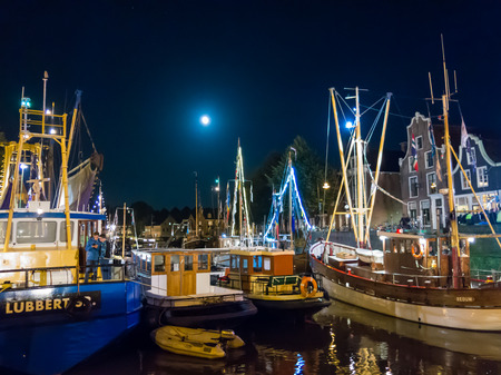 DOKKUM, NETHERLANDS - SEP 9, 2017: Boats in historic harbour at night during event Admiralty Days in old town of Dokkum, Friesland, Netherlands Redactioneel