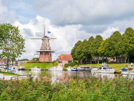 Motorboats on canal and windmill on fortifications of historic fortified town of Dokkum, Friesland, Netherlands