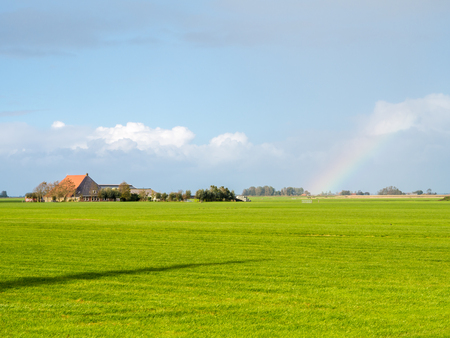 Polder landscape with pasture, farmhouse and rainbow near city of Workum, Friesland, Netherlands
