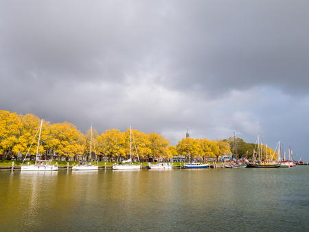 Sailboats moored at jetty in marina, trees in autumn colours and storm clouds, Enkhuizen, Noord-Holland, Netherlands