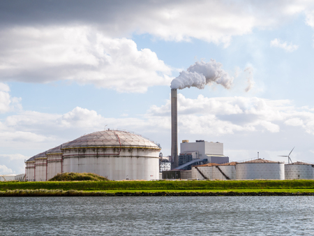 Oil storage tanks and exhaust stack of power station Hemweg in Westpoort, Port of Amsterdam, North Sea Canal, Netherlands Redactioneel