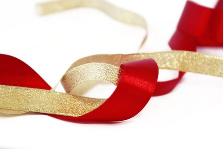 goldish: Ribbons: red satin and goldish on a white background.