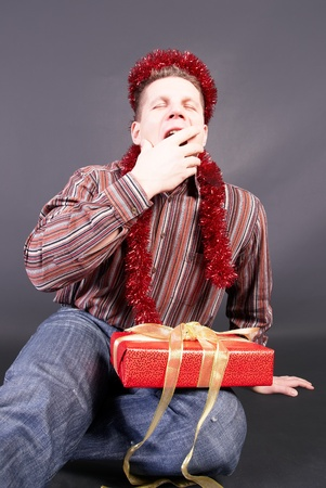dullness: A man yawns, laying  the not opened gift on knees                    Stock Photo
