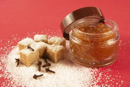 body scrub: Body scrub with brown sugar crystals, spicinesses, on a red background