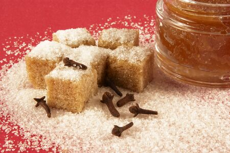 body scrub: Body scrub with brown sugar crystals, spicinesses, on a red background                        Stock Photo