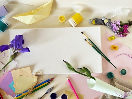 Paper boat, colored paper, brushes and canvas for inspiration and creativity