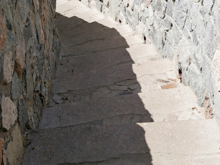 The texture of the old stone staircase with a spiral descending downwards, in the afternoon, illuminated by the sun, the ancient architecture in the natural environment Stock Photo