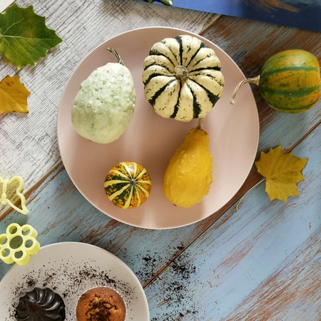 Autumn composition of pumpkins of different varieties, cupcakes, pears, cookie shapes, preparation of dessert for the holiday on a light wooden background, helloween, top view