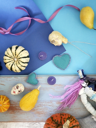 Decorative composition of pumpkins, pears, stitched dolls and felt hearts on a blue background from different textures, top view, helloween, concept of preparation for a home seasonal holiday Stock Photo