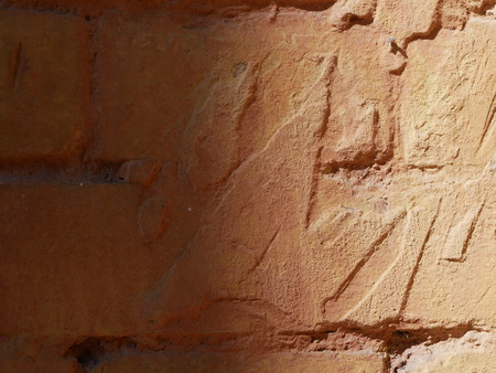 Texture of an old red brick wall with shadows of solar lighting