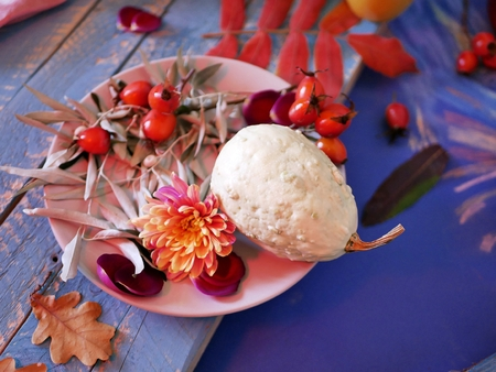 leaves, pumpkins, apples and rose petals on wooden table