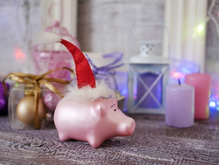 Christmas toy piglets in Santas red hats, festive illumination, candles 版權商用圖片