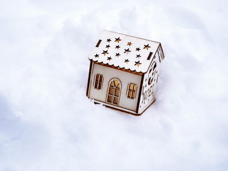 toy decorative house with lighted illumination on the snow