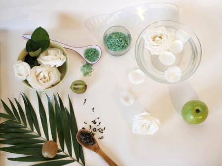 White roses, petals, sea salt, light table, top view
