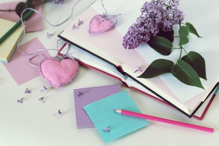 Open book, bookmarks, hearts, paper, pencils, branches of lilac flowers 스톡 콘텐츠