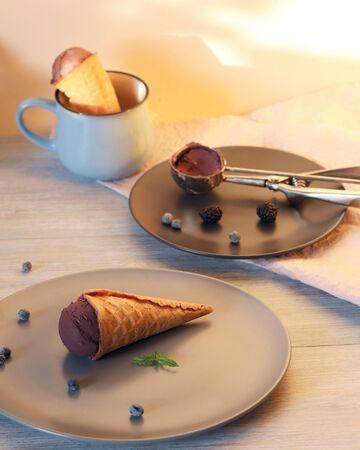 Homemade chocolate ice cream in waffle cones, berries