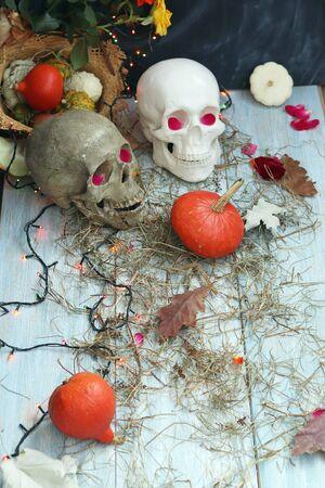 Halloween composition made of imitation skull, pumpkins, roses