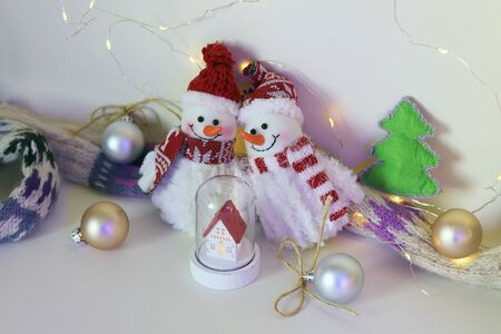 A pair of toy cheerful snowmen with a Christmas tree toy, decor