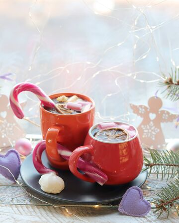 Two cups with a hot drink, marshmallows, caramel sticks, Christmas decor, hearts, illuminations