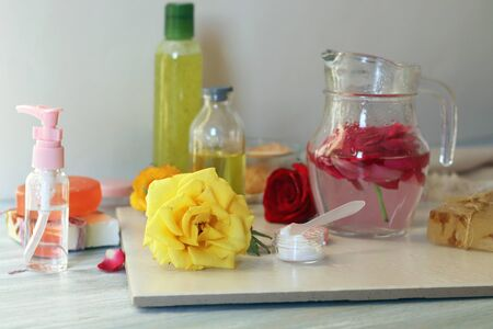 Fresh roses, petals, water and oil on the table for the preparation of natural cosmetics, spa treatments