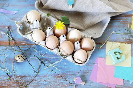 Fresh eggs in the package, Easter decoration on a wooden background, top view