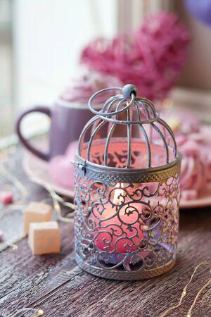 촛불 장식 랜턴, 커피 한 잔, 디저트, 창문 배경의 낭만적인 장식, 가정적인 분위기, 발렌타인 데이