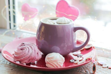 Cup of coffee with meringues and marshmallows, hearts, illumination on a wooden windowsill, home comfort, St. Valentine's Day