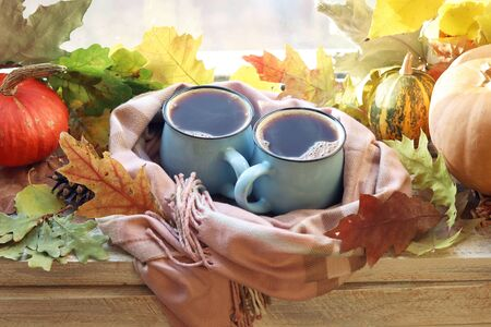 Two cups of coffee, pumpkins, leaves on a window background, the concept of home comfort, family privacy, Thanksgiving, autumn season