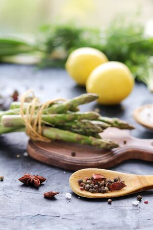 Fresh herbs, asparagus, lemons, spices on the kitchen table for preparing healthy homemade food from organic products