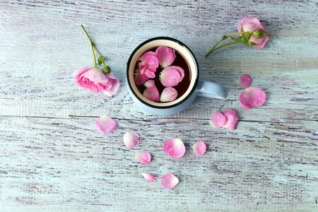 Cup of tea with rose petals, fresh flowers on a wooden surface, top view, romantic breakfast