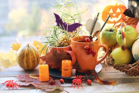 Halloween decor, a couple of cups with a drink, decorative candles, pumpkins, leaves on the windowsill, autumn seasonal holidays, the concept of home comfort