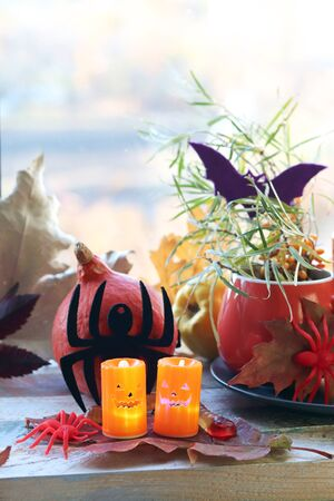 Halloween decor, cup with a drink, decorative candles, pumpkins, leaves on the windowsill, autumn seasonal holidays, home comfort concept Stock Photo