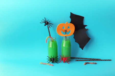 Happy Halloween, bottles with green cocktail, mystical decor on a bright background, home interior for the holiday Stok Fotoğraf