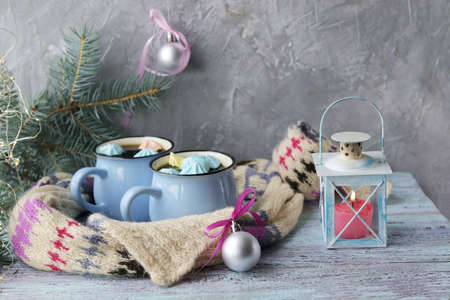 Two cups of coffee with meringues, Christmas decor, decorative lantern with a burning candle on a wooden surface on a window background, concept of family winter holidays